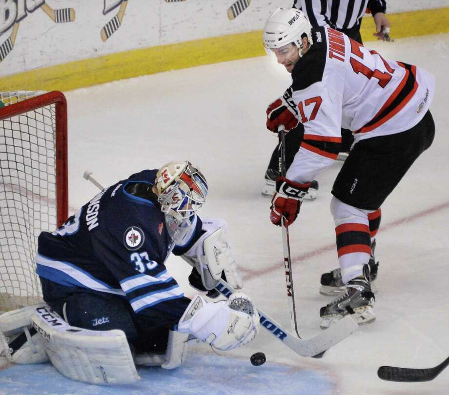 Albany Devils' #17 Scott Timmins, right, has his shot blocked by St. John's IceCaps goalie Michael Hutchinson during the second game of a best-of-5 American Hockey League playoff series at the Times Union Center Saturday April 26, 2014, in Albany, NY.   (John Carl D'Annibale / Times Union) Photo: John Carl D'Annibale / 00026569A
