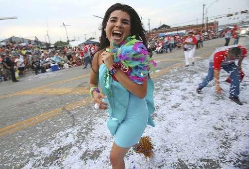 Ara Celi runs to escape a confetti ambush during the Fiesta Flambeau Night Parade in downtown San Antonio  on April 26, 2014. Photo: Tom Reel, San Antonio Express-News