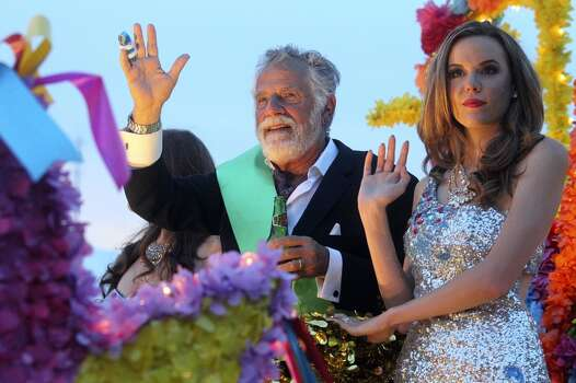 """The """"Most Interesting Man in the World"""" waves at the crowd on Broadwya during the Fiesta Flambeau Night Parade in downtown San Antonio  on April 26, 2014. Photo: Tom Reel, San Antonio Express-News"""