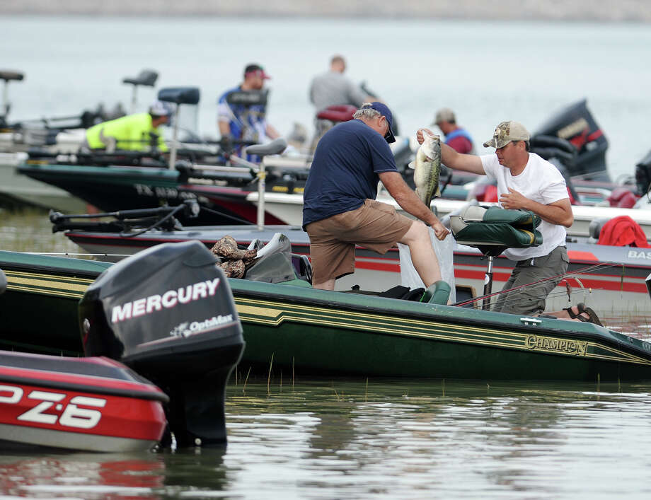 Mike Ham, left, and Daniel Roberson haul out their catch to have it weighed during the Big Bass Splash on Saturday morning. The Big Bass Splash was held on Lake Sam Rayburn in Jasper, Texas, from April 25-27. Nicole Sealy, tournament operations manager, said that over 5,000 anglers had entered the competition by Saturday morning. Photo taken Saturday, 4/26/14 Jake Daniels/@JakeD_in_SETX Photo: Jake Daniels / ©2014 The Beaumont Enterprise/Jake Daniels