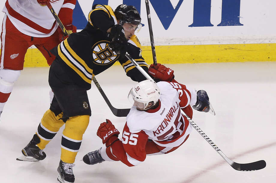 The Bruins' Brad Marchand (left) checks the Red Wings' Niklas Kronwall during the third period. After losing Game 1, the Bruins won four straight to clinch the first-round series. Photo: Michael Dwyer / Associated Press / AP
