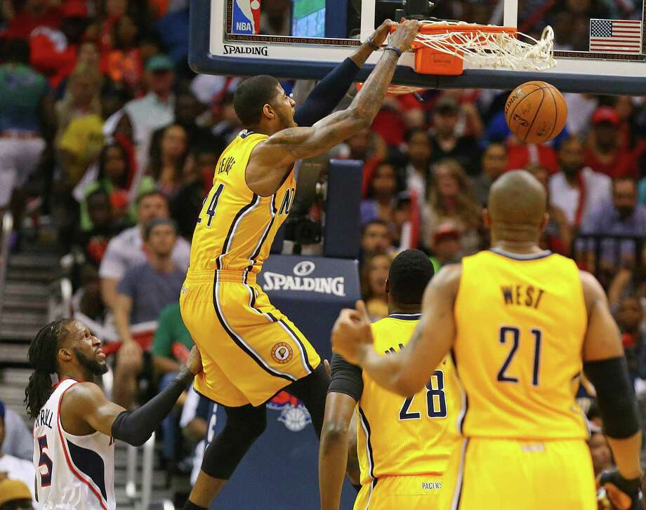 Indiana's Paul George gets past Atlanta's DeMarre Carroll along the baseline for a dunk in the second half. George wound up with 24 points, 10 rebounds and five assists as the Pacers evened the series 2-2. Photo: Curtis Compton / Atlanta Journal-Constitution / Atlanta Journal-Constitution