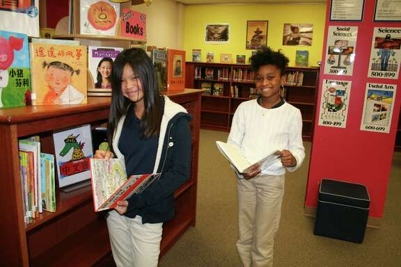 Andrea Chang, left, and Tyla-Simone Crayton check out books in Mandarin Chinese in the St. George Place Elementary School library. To reach more students with  reading material in multiple languages, St. George Place's PTO donated funds to buy Kindles for each classroom and e-books in various languages.