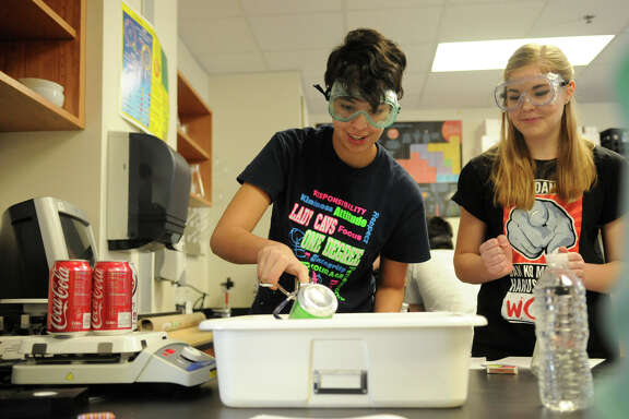 The Woodlands College Park High School sophomores Maya Vasquez, left, and Annmarie Janning team up on a project in chemistry class.