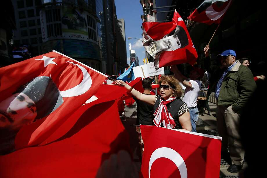 People wave Turkish flags as they take part in a protest in support of Turkey's position on the 1915 mass killing of Armenians in the Ottoman Empire, at Times Square in New York April 26, 2014. The exact nature and scale of what happened during fighting that started in 1915 is highly contentious and continues to sour relations between Turkey and Armenia, a former Soviet republic. Turkey accepts that many Armenians died in clashes, but denies that up to 1.5 million were killed and that this constituted an act of genocide - a term used by many Western historians and foreign parliaments. REUTERS/Eduardo Munoz (UNITED STATES - Tags: POLITICS CIVIL UNREST) Photo: Eduardo Munoz, Reuters