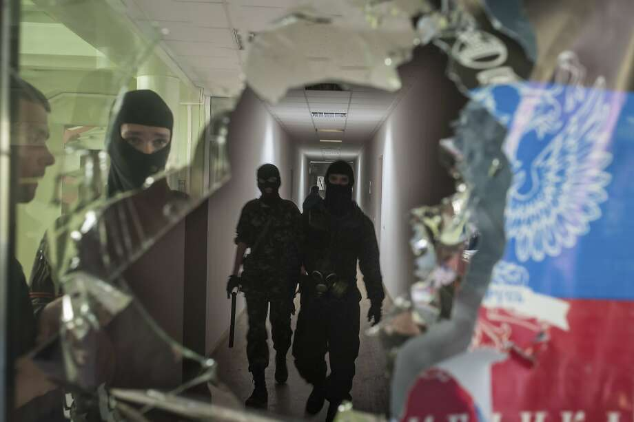 Masked pro-Russian militants patrol in the local administration building in Mariupol, Ukraine, Saturday, April 26, 2014. A pro-Russian insurgency leader in eastern Ukraine said Saturday that foreign military observers detained as suspected NATO spies could be released in exchange for jailed pro-Russian activists. (AP Photo/Evgeniy Maloletka) Photo: Evgeniy Maloletka, Associated Press