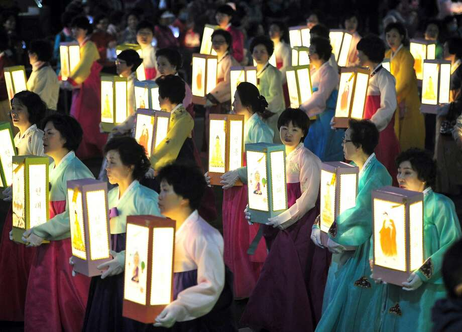 TOPSHOTS-South Korean Buddhist followers march with lanterns tied with yellow ribbons of hope for a safe return for missing passengers of the sunken South Korean ferry 'Sewol' during the Lotus Lantern Festival in downtown Seoul on April 26, 2014. Buddhists dedicated an annual lotus lantern festival, the highlight of its celebrations for Buddha's birthday, to those killed in the accident and pray for the safe return of possible survivors.  AFP PHOTO / JUNG YEON-JEJUNG YEON-JE/AFP/Getty Images Photo: Jung Yeon-je, AFP/Getty Images