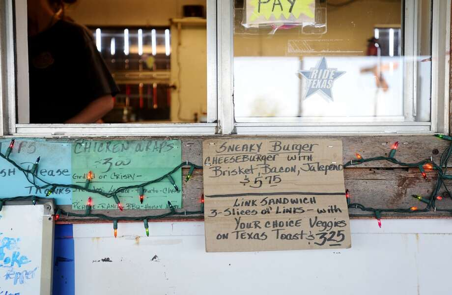 A handmade sign advertising a signature dish -- the Sneaky Burger -- sits below the ordering window at Sneaky Pete's on Tuesday. Sneaky Pete's has been doling out burgers and loaded potatoes in Groves since 2009. The restaurant is open from Monday to Saturday, from 10 am to 6 pm, and delivers to local businesses from 10 am to 1pm. Photo taken Tuesday, 4/15/14 Jake Daniels/@JakeD_in_SETX