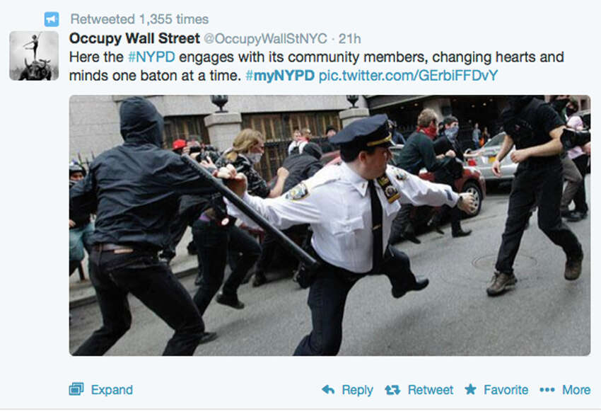 This frame grab from a Twitter post from @OccupyWallStNYC shows a news photo of a New York City police officer wielding a baton during an Occupy Wall Street action in New York. The photo was posted in response to a Twitter request by the NYPD to offer up feel-good photos of people posing with police officers. NYPD Commissioner William Bratton on Wednesday, April 23, 2014 admits he was caught off guard by the harsh response to a harmless attempt at community outreach on Twitter, but says he has no plans to abandon social media.