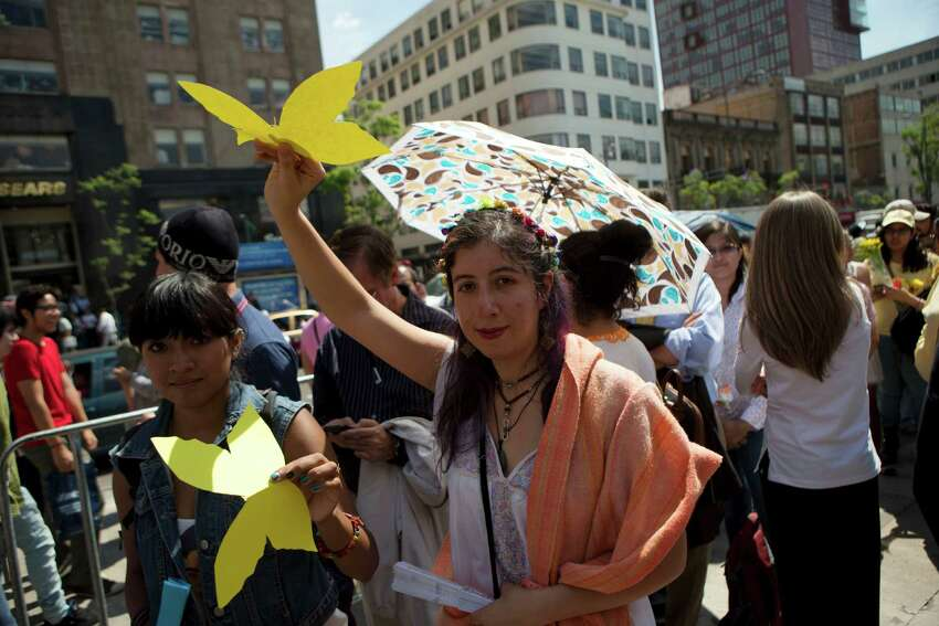 Well-wishers carry yellow butterflies as they wait in line outside the Palace of Fine Arts to pay their respects to Colombian Nobel Literature laureate Gabriel Garcia Marquez, in Mexico City, Monday, April 21, 2014. The ashes of Garcia Marquez were taken Monday to Mexico City's majestic Palace of Fine Arts, where thousands of admiring readers began paying tribute to the Colombian Nobel laureate considered one of the greatest Spanish-language authors of all time.