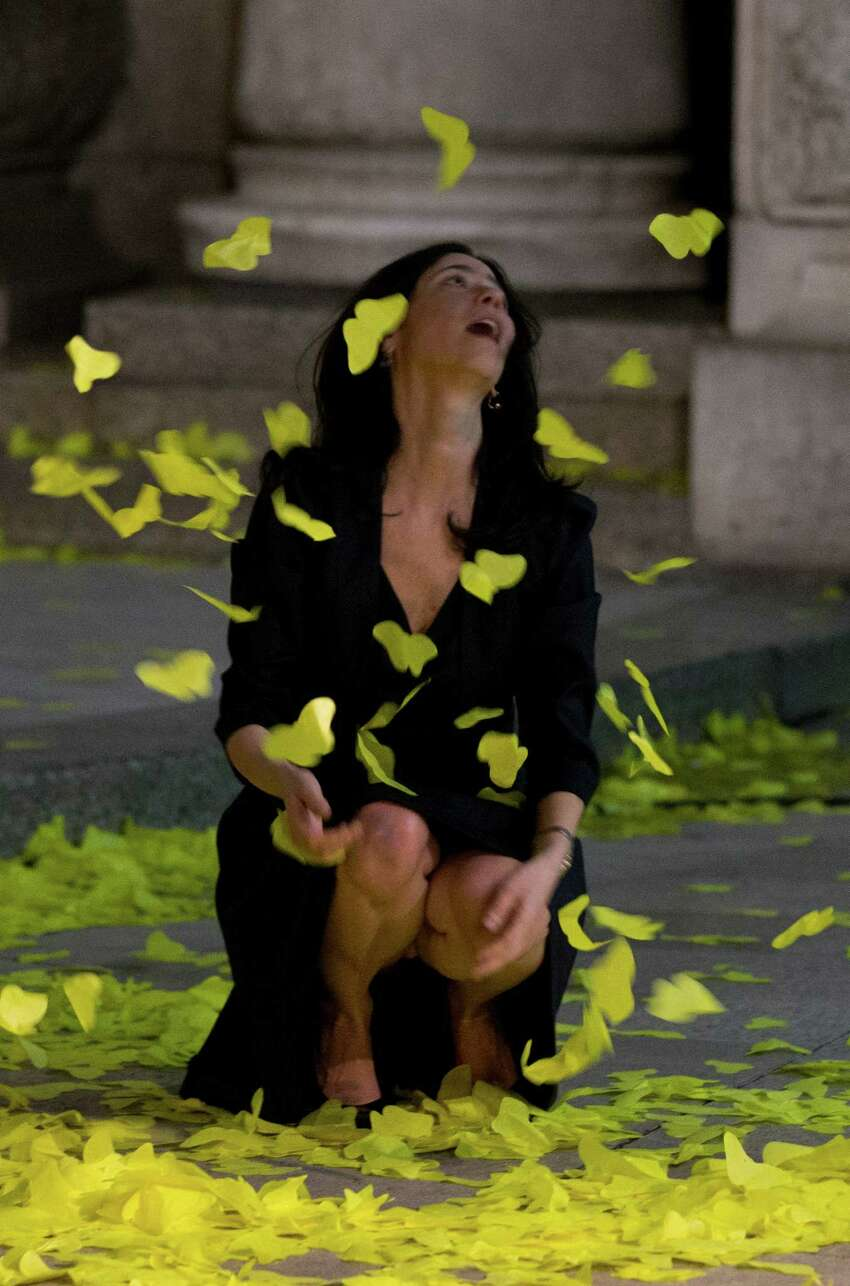 A guest leaving a memorial service for Gabriel Garcia Marquez plays in yellow paper butterflies outside the Palace of Fine Arts in Mexico City, Monday, April 21, 2014. Garcia Marquez, known throughout Latin American and much of the world simply as