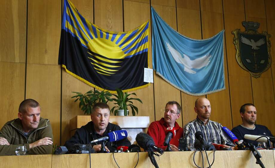 Vacheslav Ponomarev (second from left), the self- proclaimed mayor of Slovyansk, is flanked by foreign observers being held by his group as he addresses the media. Photo: Sergei Grits, Associated Press