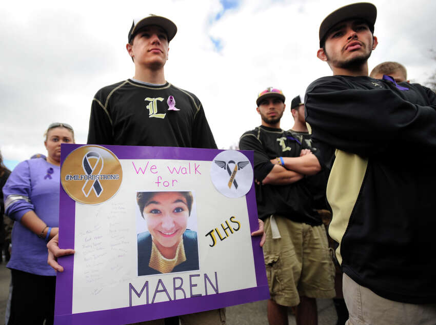 Jonathan Law High School baseball player Kurt Holden holds a sign in memory of classmate Maren Sanchez as he walked with his teammates in her honor at the annual In Your Shoes event at Lisman Landing in downtown Milford, Conn. on Sunday, April 27, 2014.