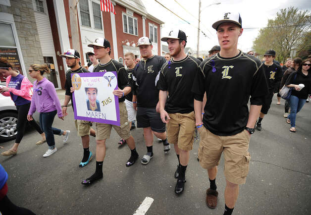 Jonathan Law High School baseball player Kurt Holden holds a sign in memory of classmate Maren Sanchez as he walks with his teammates in her honor at the annual In Your Shoes event on Broad Street in downtown Milford, Conn. on Sunday, April 27, 2014. Photo: Brian A. Pounds / Connecticut Post