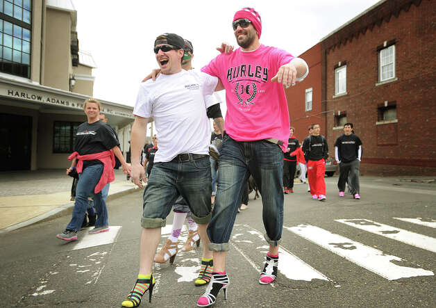 Troy Kovalik, left, and Ryan Robstock, both of Milford, help to keep each other from toppling over as they walk in high heels during the 8th annual In Your Shoes event  in downtown Milford, Conn. on Sunday, April 27, 2014. The walk raises money for The Rape Crisis Center, of Milford. Photo: Brian A. Pounds / Connecticut Post
