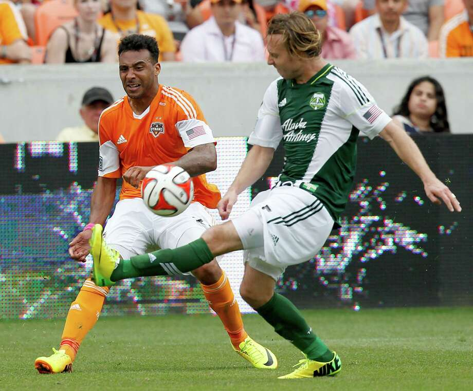 Portland Timbers defender/midfielder Michael Harrington (5) kicks the ball away from Houston Dynamo midfielder Giles Barnes (23) at BBVA Compass Stadium in Houston, Texas. Dynamo and Portland draw 1 to 1. Photo: Thomas B. Shea, For The Chronicle / © 2014 Thomas B. Shea