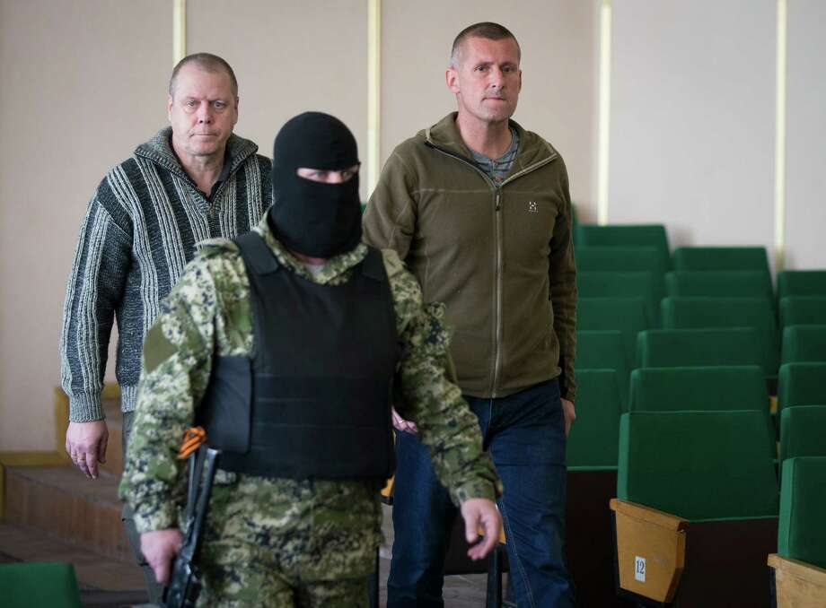 John Christensen, right, a senior Sgt. in the Danish army and his colleague, both members of a group of foreign military observers are escorted by a pro-Russian militant to attend a press conference in the city hall of Slovyansk, eastern Ukraine, Sunday, April 27, 2014. As Western governments vowed to impose more sanctions against Russia and its supporters in eastern Ukraine, a group of foreign military observers remained in captivity Saturday accused of being NATO spies by a pro-Russian insurgency. The German-led, eight-member team was traveling under the auspices of the Organization of Security and Cooperation in Europe when they were detained Friday. (AP Photo/Alexander Zemlianichenko) Photo: Alexander Zemlianichenko, STF / AP