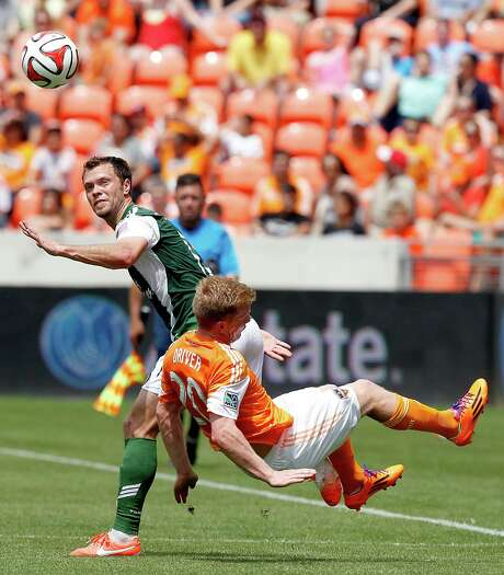 Dynamo midfielder Andrew Driver, right, gets the worst of an encounter with the Timbers' Diego Valeri. Photo: Thomas B. Shea, Freelance / © 2014 Thomas B. Shea