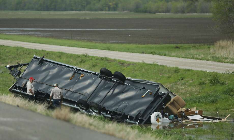 Motorists check out a travel trailer damaged in an accident involving high winds from a severe thunderstorm that passed near Rich Hill, Mo., Sunday, April 27, 2014. (AP Photo/Orlin Wagner) Photo: Orlin Wagner, Associated Press