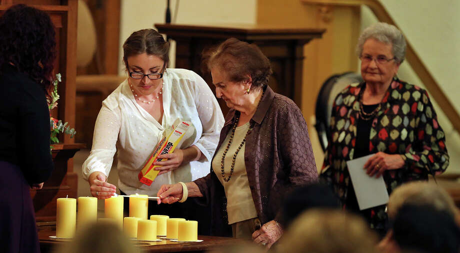 Sophia Cathcart, Special Program Manager at the Holocaust Memorial Museum of the Jewish Federation of San Antonio, (from left) helps Holocaust survivors Susanne Jalnos, 87, and Anna Rado, 83 who are sisters light candles during the Yom HaShoah commemoration Sunday April 27, 2014 at Temple Beth-El. Photo: Edward A. Ornelas, San Antonio Express-News / © 2014 San Antonio Express-News