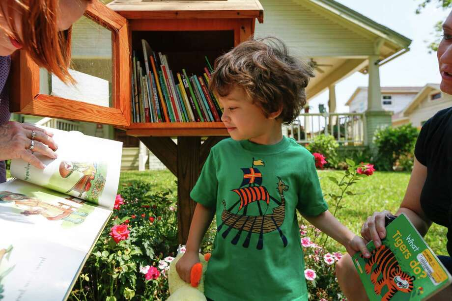 "Ivan O'Sullivan, 2, visits a Little Free Library in his East End neighborhood. The tiny book depots are a growing trend of ""take one, leave one"" libraries run by individuals. Photo: Eric Kayne / Eric Kayne"