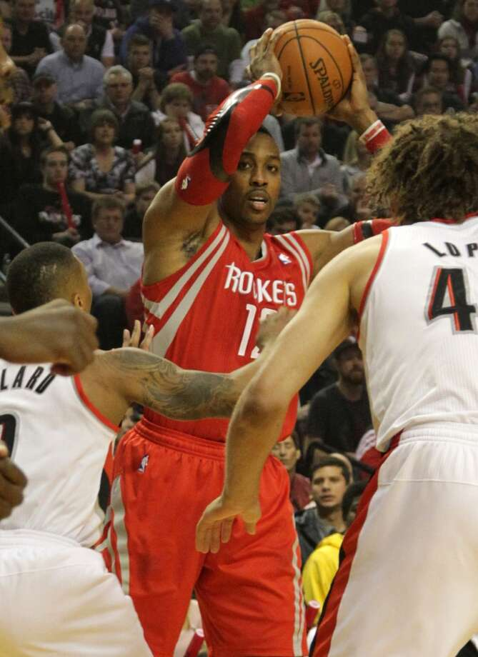 Rockets center Dwight Howard  looks to pass over Portland Trail Blazers guard Damian Lillard center Robin Lopez. Photo: James Nielsen, Houston Chronicle