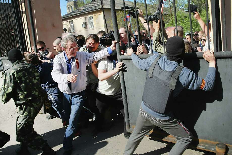 Pro-Russian activists — breaking through the gate in front of a TV station in Donetsk, Ukraine — say they were sick of watching news aired through the prism of their enemies in Kiev. Photo: Scott Olson / Getty Images / 2014 Getty Images