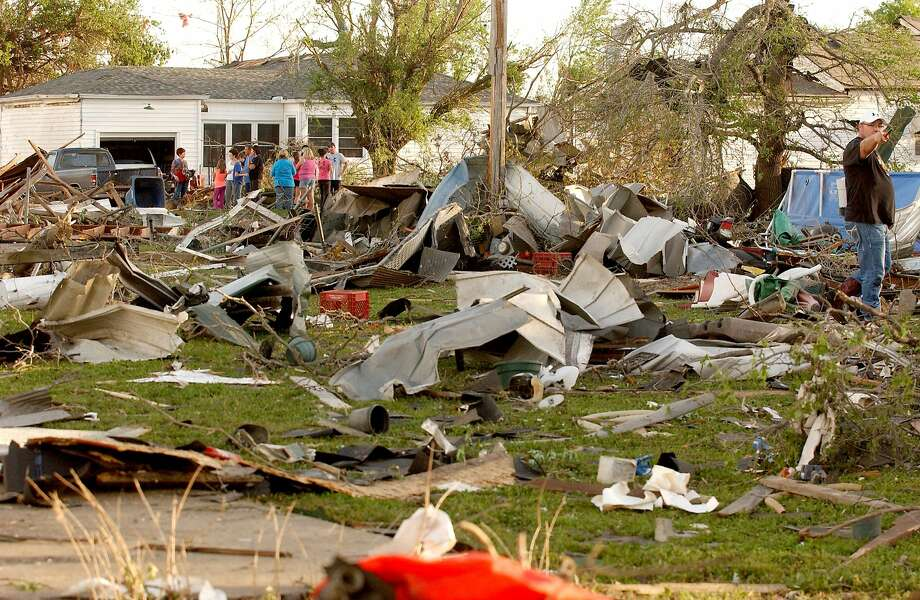 Residents of Quapaw, Okla., survey damage caused by a tornado that killed one person, injured at least six others and extensively damaged a fire station. Photo: Gary Crow, Associated Press