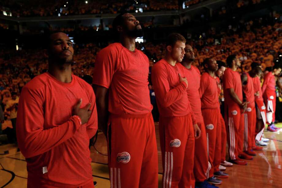 Members of the Los Angeles Clippers listen to the national anthem before Game 4 of an opening-round NBA basketball playoff series against the Golden State Warriors on Sunday, April 27, 2014, in Oakland, Calif. The Clippers chose not to speak publicly about owner Donald Sterling. Instead, they made a silent protest. The players wore their red Clippers' shirts inside out to hide the team's logo. (AP Photo/Marcio Jose Sanchez) ORG XMIT: OAS106 Photo: Marcio Jose Sanchez / AP