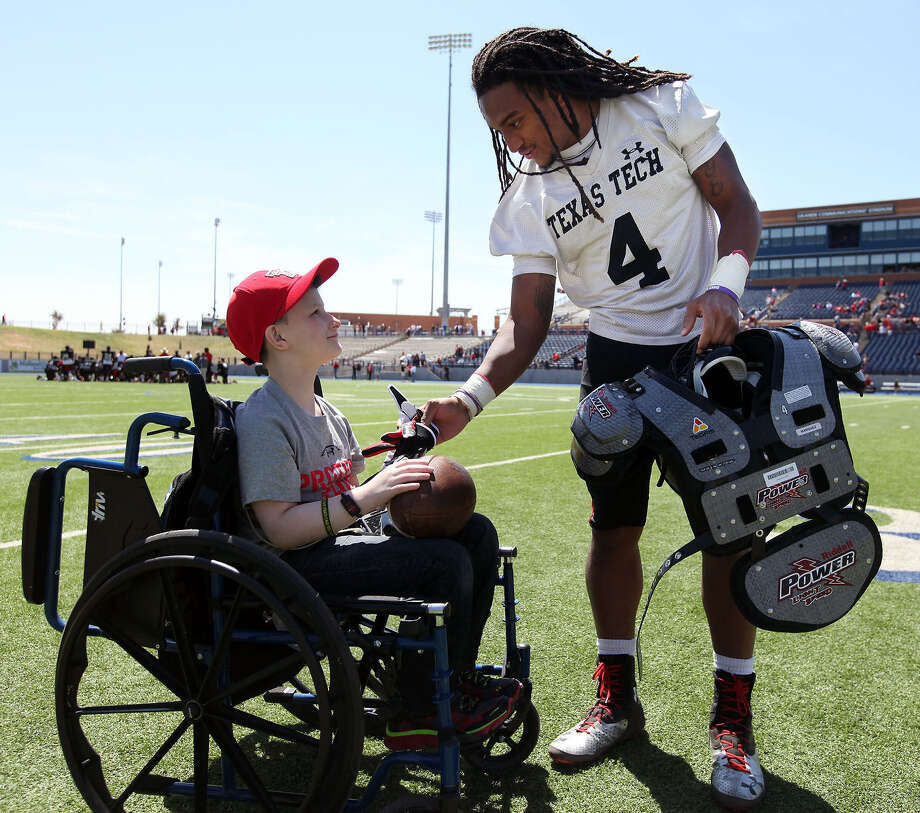 Texas Tech wide receiver Bradley Marquez, handing his gloves to 8-year-old Caden Creswell of Midland, received a $325,000 signing bonus from the New York Mets after he was selected in the 16th round of the 2011 draft but is concentrating on football for now. Photo: Edyta Blaszczyk / Odessa American / Odessa American