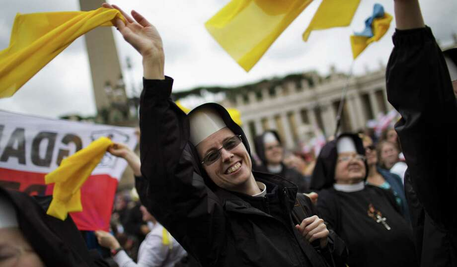 Nuns wave as Pope Francis is driven through the crowd after the canonization Mass at St. Peter's Square at the Vatican. Photo: Emilio Morenatti, Associated Press / AP