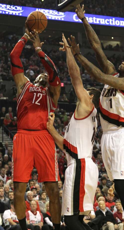 Rockets center Dwight Howard  shoots with Trail Blazers center Joel Freeland, center, and forward Dorell Wright, right, defending. Photo: James Nielsen, Houston Chronicle