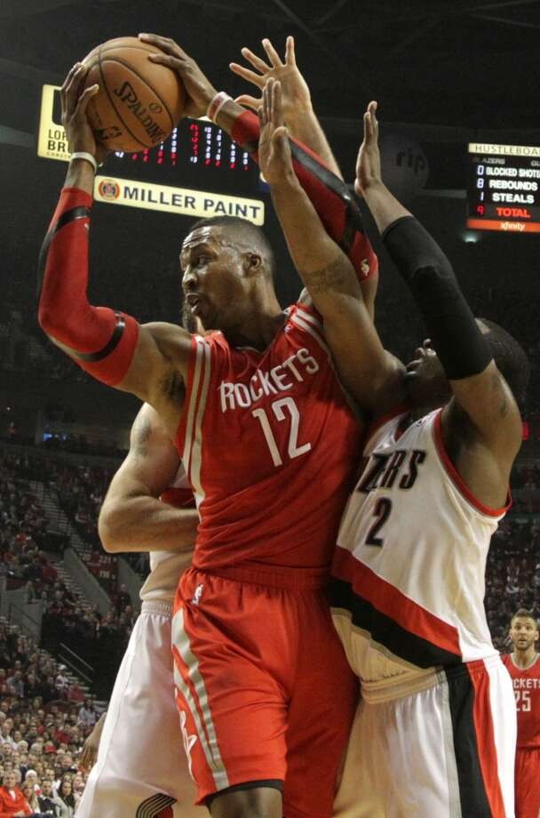 Rockets center Dwight Howard  pulls down a rebound. Photo: James Nielsen, Houston Chronicle
