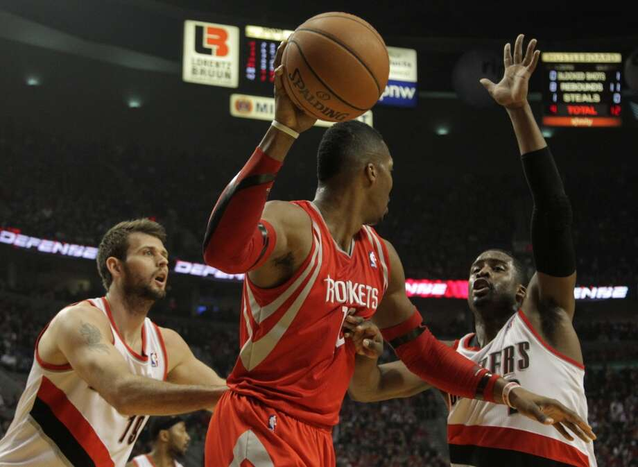 Rockets center Dwight Howard looks to pass with Trail Blazers center Joel Freeland, left, and guard Wesley Matthews defending. Photo: James Nielsen, Houston Chronicle