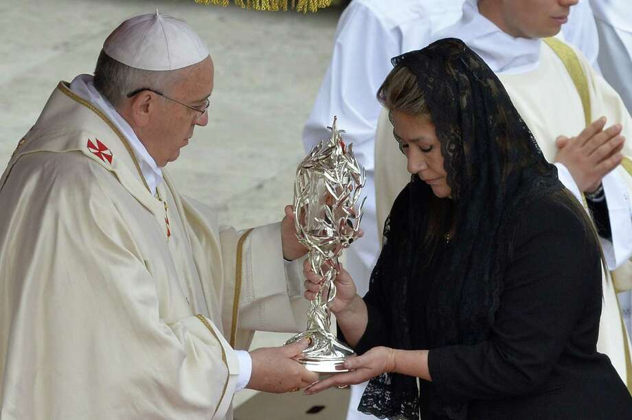 A woman offers a relic to Pope Francis in Rome, April, 2014. File photo. Photo: ANDREAS SOLARO, Staff / ANDREAS SOLARO