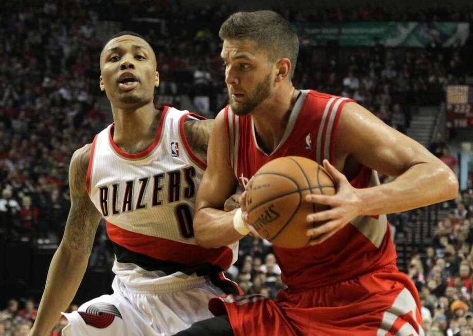 Rockets forward Chandler Parsons runs past Trail Blazers guard Damian Lillard. Photo: James Nielsen, Houston Chronicle
