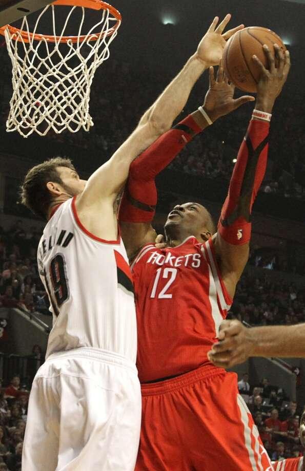 Rockets center Dwight Howard  shoots against Trail Blazers center Joel Freeland. Photo: James Nielsen, Houston Chronicle