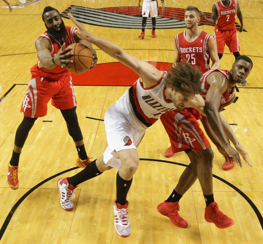 Rockets guard James Harden, left, grabs a rebound away from Trail Blazers center Robin Lopez, with Terrence Jones (6) and Chandler Parsons (25) in on the play. Photo: James Nielsen, Houston Chronicle