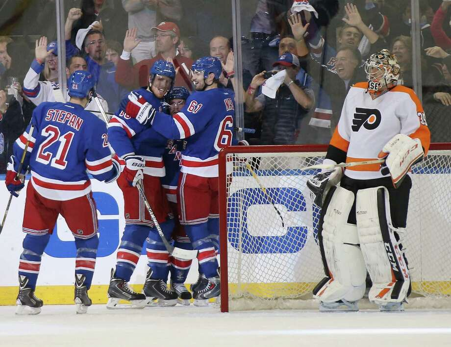 NEW YORK, NY - APRIL 27: Marc Staal #18 of the New York Rangers (second from left) celebrates his goal at 11:53 of the first period against Steve Mason #35 of the Philadelphia Flyers along with Derek Stepan #21 (L) Martin St. Louis #26 (C) and Rick Nash #61(R) in Game Five of the First Round of the 2014 NHL Stanley Cup Playoffs at Madison Square Garden on April 27, 2014 in New York City.  (Photo by Bruce Bennett/Getty Images) ORG XMIT: 485353657 Photo: Bruce Bennett / 2014 Getty Images