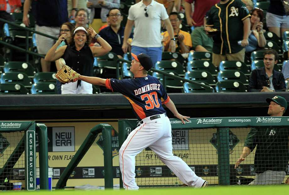 Astros third baseman Matt Dominguez manages to negotiate the railing and opening to the dugout while catching a popup hit by Coco Crisp in the first inning Sunday. Photo: Mayra Beltran, Staff / © 2014 Houston Chronicle