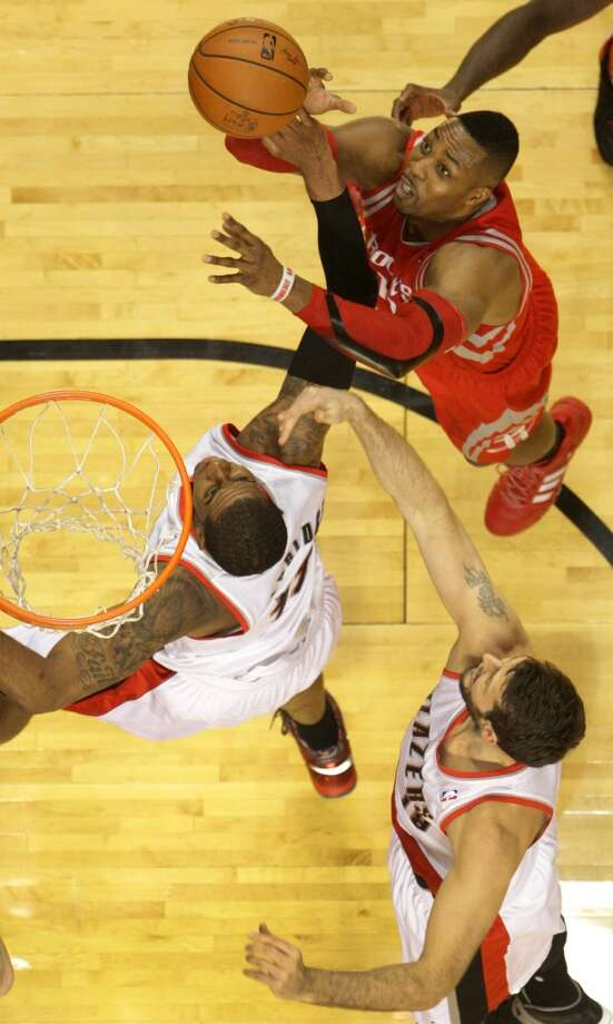 Houston Rockets center Dwight Howard, top, grabs a rebound away from Portland Trail Blazers forward LaMarcus Aldridge (12) and center Joel Freeland (19) during the first half of Game 4 of the Western Conference Quarterfinals playoffs at the Moda Center Sunday, April 27, 2014, in Portland. ( James Nielsen / Houston Chronicle ) Photo: James Nielsen, Houston Chronicle