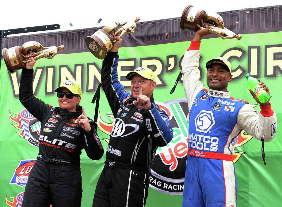 Pro stock champion Erica Enders-Stevens, left, funny car champion Robert Hight, center, and top fuel champion Antron Brown raise their trophies at the 27th annual O'Reilly Auto Parts NHRA Spring Nationals, Sunday, April 27, 2014, at Royal Purple Raceway in Baytown, TX. Photo: Eric Christian Smith, For The Chronicle