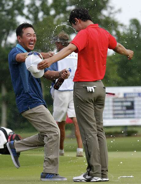 South Korean golfer Charlie Wi (left) douses countryman Seung-Yul Noh with beer after his first PGA Tour victory at the Zurich Classic. Photo: Bill Haber / Associated Press / FR170136 AP