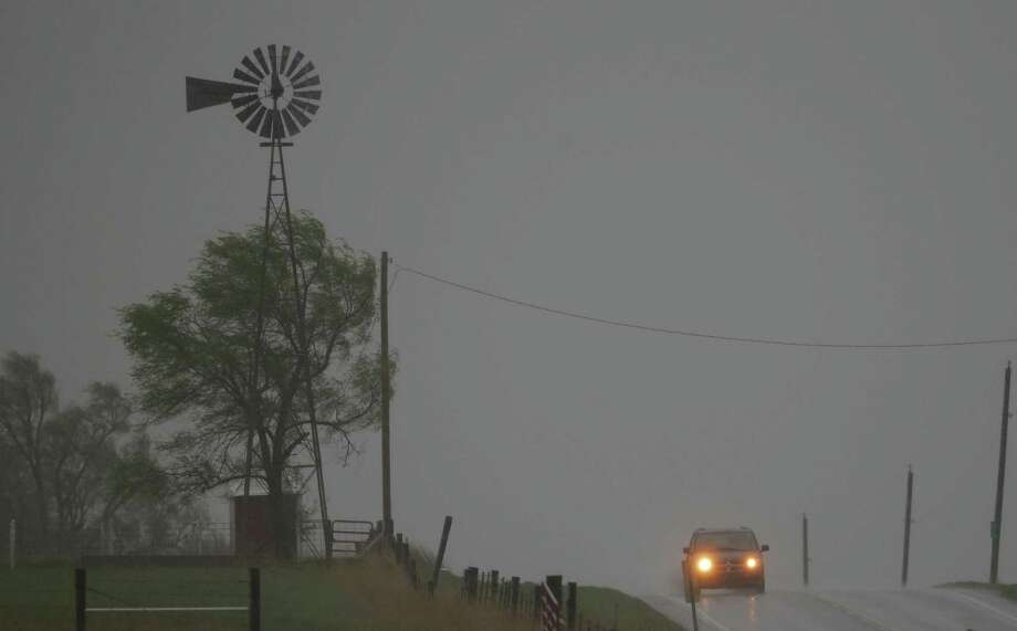 An SUV tops a hill along U.S. Route 56 as a severe thunderstorm moves through Baldwin City, Kan. Photo: Orlin Wagner, Associated Press / AP