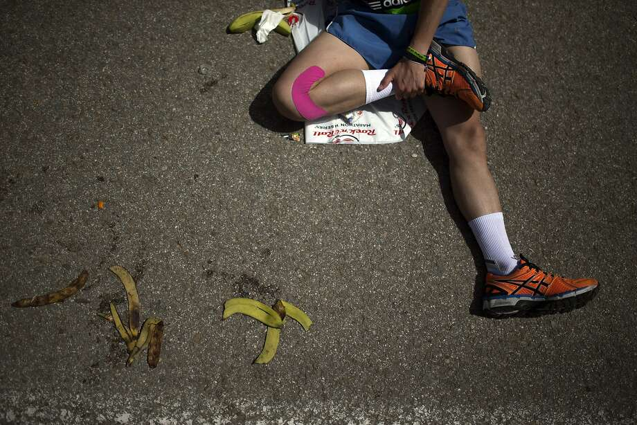 A runner stretches after he crossing the finish line in the 37th Madrid Marathon in Madrid, Spain, Sunday, April 27, 2014. (AP Photo/Andres Kudacki) Photo: Andres Kudacki, Associated Press