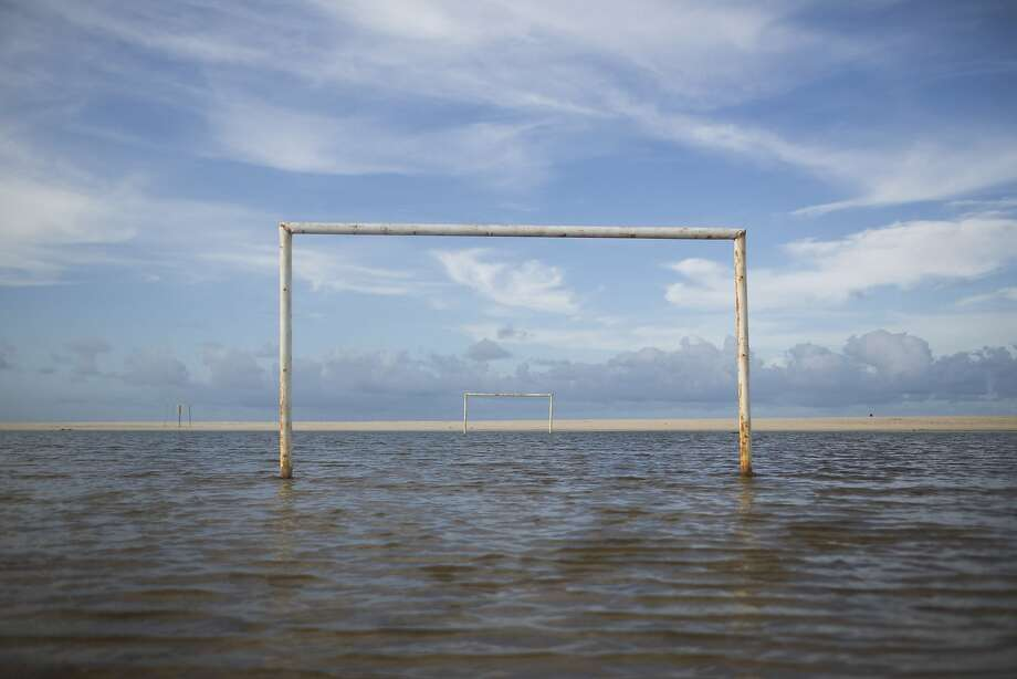 A soccer field is seen under the water during a high tide in Beberibe near Fortaleza, Brazil, Saturday, April 26, 2014. Beberibe is one of the coast cities located south-east of Fortaleza with many magnificent beaches popular with tourists. Fortaleza one of the host cities of the 2014 soccer World Cup. (AP Photo/Felipe Dana) Photo: Felipe Dana, Associated Press