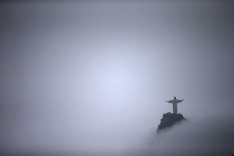 Christ the Redeemer statue seen from Santa Marta slum as surrounded by clouds, in Rio de Janeiro, Brazil, Sunday, April 27, 2014. The Christ the Redeemer statue Christ the Redeemer is a statue was considered the largest Art Deco statue in the world from 1931 until 2010 when it was topped by the Christ the King statue in Poland.  (AP Photo/Hassan Ammar) Photo: Hassan Ammar, Associated Press