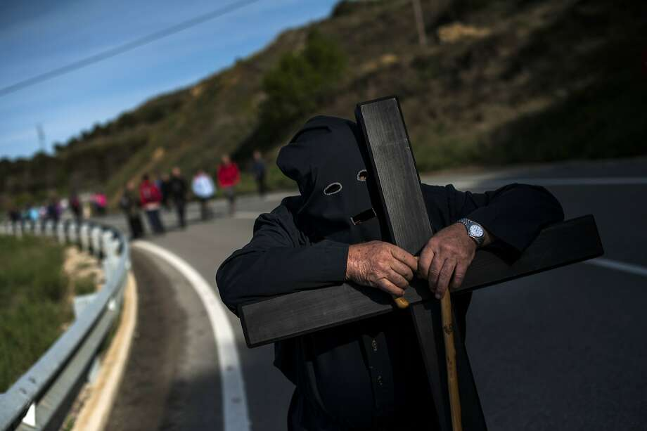 A masked Catholic penitent rests on a cross while participating in a pilgrimage from Tafalla to the small town of Ujue, northern Spain, Sunday, April 27, 2014. According to tradition, the pilgrimage to Ujue originated in 1043 when the residents of Tafalla made a pilgrimage to Ujue to thank the Virgin for their victory in a battle. (AP Photo/Alvaro Barrientos) Photo: Alvaro Barrientos, Associated Press