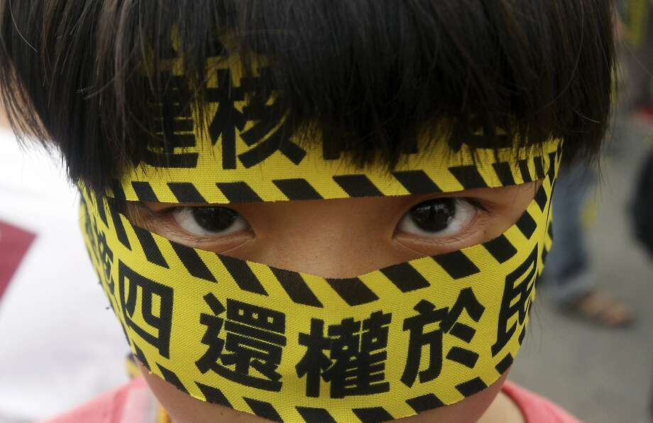"A Taiwanese boy wears a slogan reading ""Stop the 4th Nuclear Power Plant. Give Power Back to People,"" during a protest against the construction of Taiwan's fourth nuclear power plant to be completed in Taipei, Taiwan, Sunday, April 27, 2014. Taiwan's opposition party has long opposed nuclear power and public caution over nuclear safety has risen following the 2011 nuclear disaster in Japan. (AP Photo/Chiang Ying-ying) Photo: Chiang Ying-ying, Associated Press"