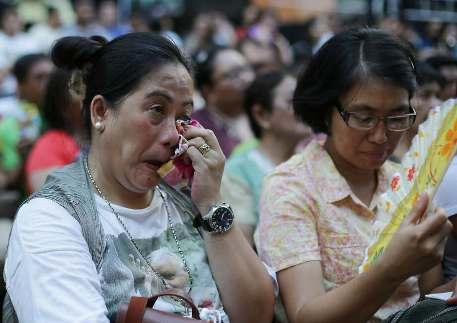 A Filipino devotee wipes tears as she watches the live satellite broadcast of the canonization or the elevation to sainthood in the Vatican of Roman Catholic Pope John Paul II and Pope John XXIII on Sunday, April 27, 2014 in suburban Quezon city, north of Manila, Philippines. Pope Francis declared his two predecessors John XXIII and John Paul II saints on Sunday before hundreds of thousands of people in St. Peter's Square, an unprecedented ceremony made even more historic by the presence of retired Pope Benedict XVI. The predominantly Roman Catholic Philippines joins several nations worldwide in the celebration of canonization of the two Popes. (AP Photo/Aaron Favila) Photo: Aaron Favila, Associated Press